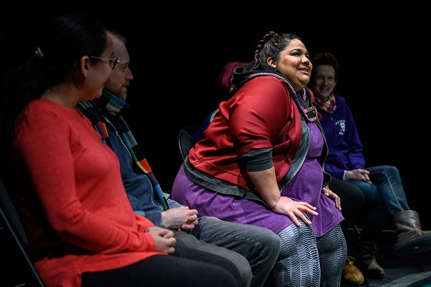 This photo shows Yolanda Bonnell sitting on a rock (which is part of the set) beside audience members during a performance of bug.