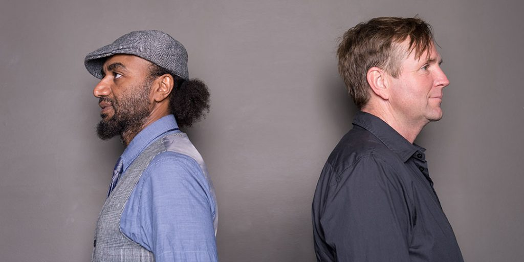 John and Waleed facing away from each other against a dark grey wall