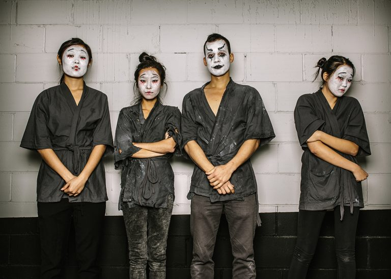 Four East Asian actors have their faces painted in white paint, with mask-like face painting. three are smiling at the camera, but one character is off to the side looking concerned.