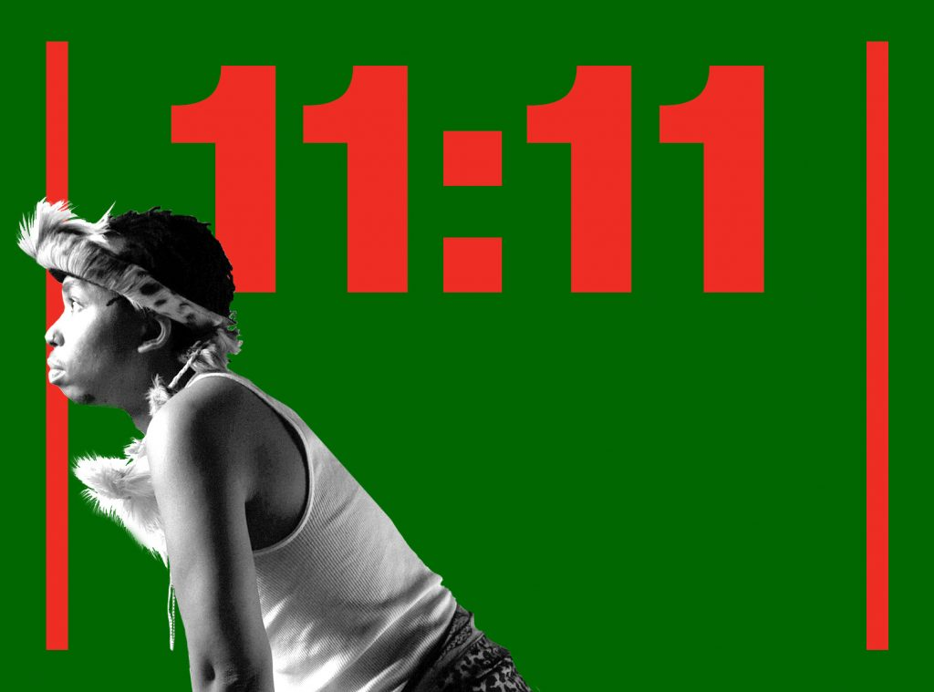 Click here to buy tickets to 11:11. Visual Description: Samson is sitting, looking into a light on the side of green graphic reading 11:11.
