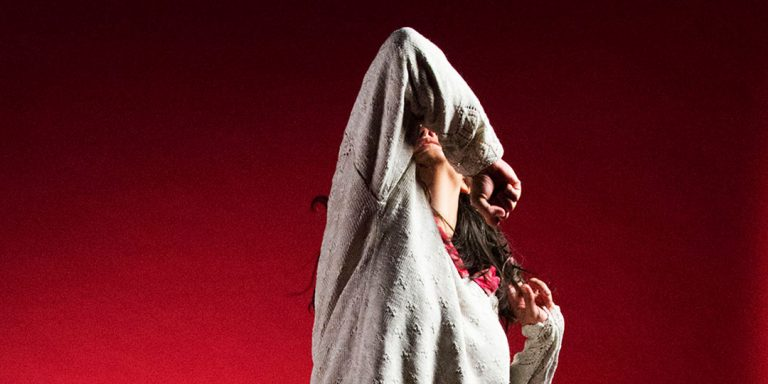 candid shot of performer dancing, against an intense red background. Elbow is pointing to the sky.