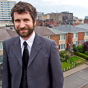 David is a tall, white man with short brown hair. He has a short beard and a moustache, and in the photo he is wearing a grey suit.