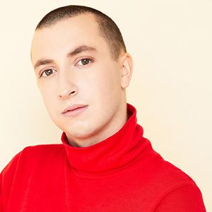 Merlin has soft features, fair skin and a clean, buzzed cut hair. In the photo they're wearing a red turtleneck shirt.