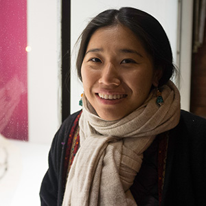 Rinchen is a Southeast asian woman with long straight black hair. In the photo she has a cozy beige scarf.