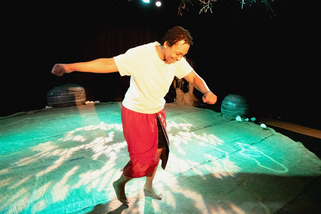 Samson is dancing happily, on the stage floor that looks like a flobe with blue lights and shadows