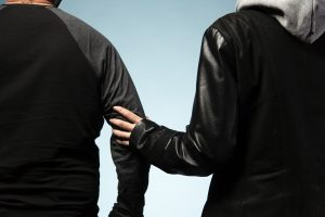 A hand is grabbing another person's arm. Both wearing dark clothes standing against a light blue backdrop