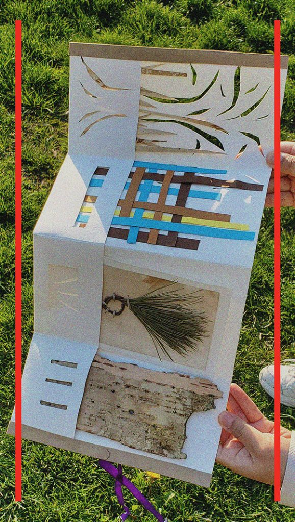 Hands are holding the accordion book out against a sunny grass. There are paper cutting shapes, weavings, grids and foraged materials inserted into the book