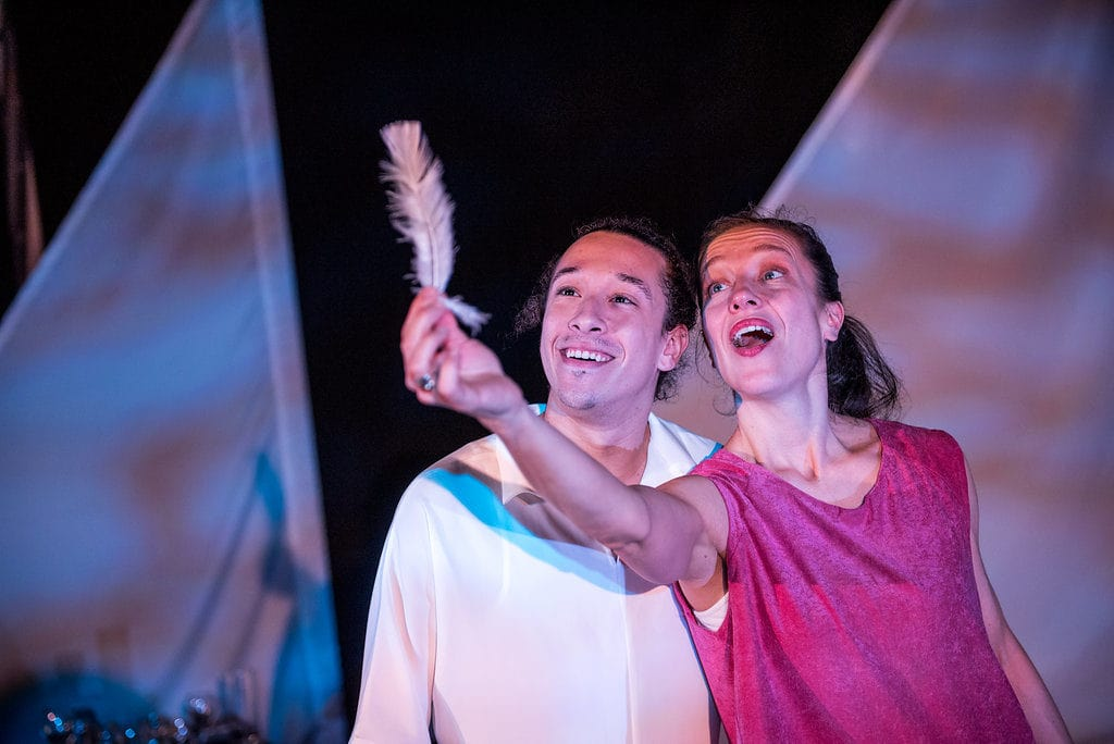 Jessica Runge and Tylee Jones are on stage, smiling and talking confidently. Jessica is holding up a feather. The lighting is pink and blue and very flow