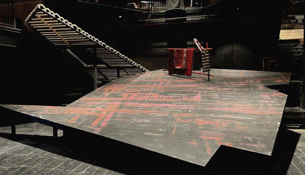 Empty stage of TOKA. The set is geometric and a complex polygonal shape. There are stairs leading it up to the balcony. It is silent