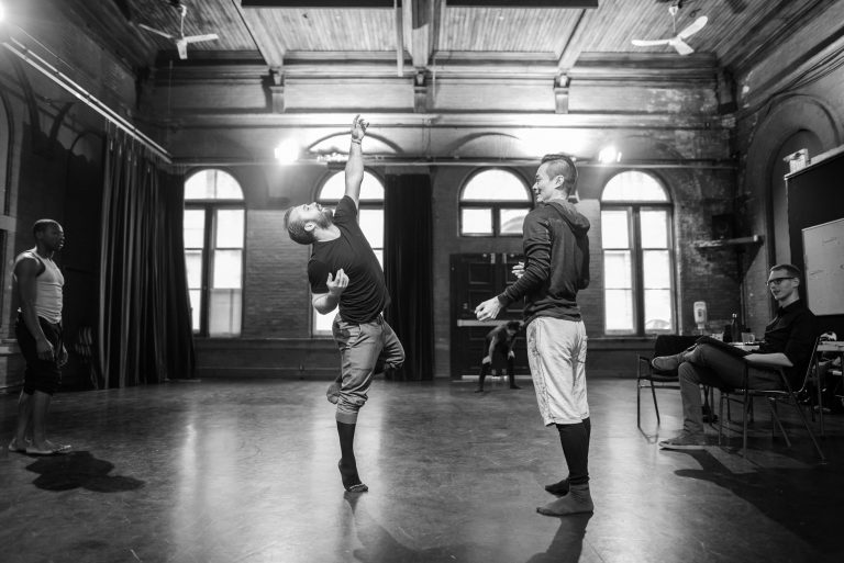 Indrit Kasapi and William Yong are choreographing in a beautiful bright studio. The photo captures a moment when Indrit strucks his arm upwards as William smiles