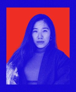 Rinchen is an East Asian Tibetan woman with long hair that comes near her hips. She has her long hair draped onto the right, wearing a turtleneck shirt and gazing into the camera