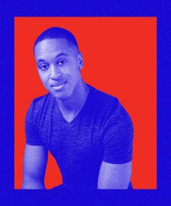 Shakeil is a Black artist with short hair. He is wearing a dark short sleeved shirt and leaning forward, smiling at the camera.