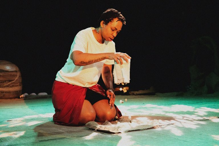 Samson Bonkeabantu Brown empties a bag of objects onto the floor while kneeled on stage.