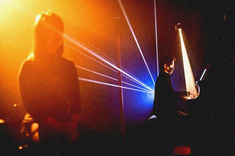 Leslie Ting is covered by fog and haze and lights while performing speculation. Hye Won Cecilia Lee is on the piano in front of the blue ray of lights.
