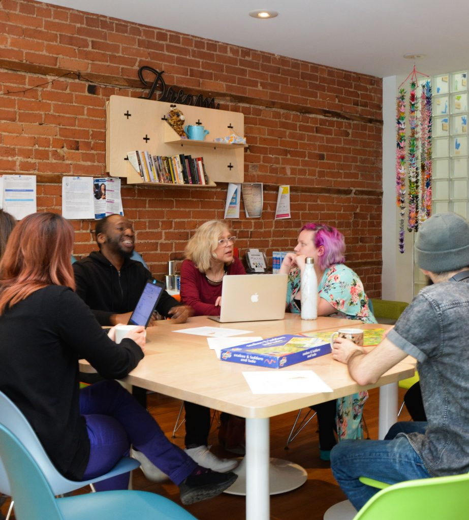Eight people sitting at a large squared table. The two people on the left are looking at a computer screen in between them while the man beside them smiles at three other people across the table. The two women in the center of the picture are in deep discussion.