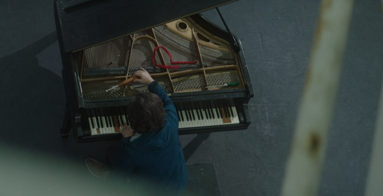 Bird eye view of a grand piano, where the performer is tuning. The theatre is dark and quiet